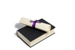 Diploma with purple bow on black book Stock Photography