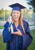 Diploma que se sostiene adolescente extático en casquillo y vestido Imagenes de archivo