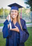 Diploma que se sostiene adolescente joven que ríe nerviosamente en casquillo y vestido Imagen de archivo libre de regalías