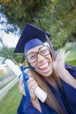 Diploma que se sostiene femenino adolescente del empollón en casquillo y vestido Imágenes de archivo libres de regalías
