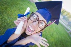 Diploma que se sostiene graduado adolescente emocionado en casquillo y vestido Fotos de archivo