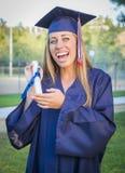 Diploma que se sostiene graduado adolescente exaltado en casquillo y vestido Foto de archivo libre de regalías