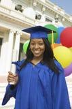 Diploma que se sostiene graduado fuera del retrato de la universidad Imagen de archivo libre de regalías