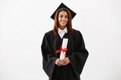 Diploma que se sostiene sonriente graduado de la hembra africana que mira la cámara sobre el fondo blanco Foto de archivo