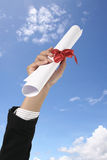 Diploma with a red ribbon. In hand on sky Stock Image