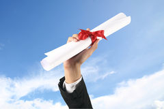 Diploma with a red ribbon. In hand on sky Stock Photos