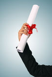 Diploma with a red ribbon. In hand  on blue background Royalty Free Stock Photography