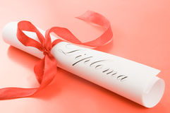 Diploma with red ribbon. On red background Royalty Free Stock Photography