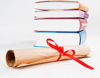 Diploma with ribbon and books Stock Photo