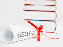 Diploma with ribbon and books Stock Photography