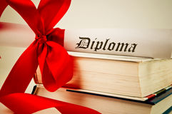 Diploma with ribbon and books Stock Images
