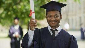 Diploma sorridente del latino-americano affascinante e di mostra laureato per la macchina fotografica, successo video d archivio