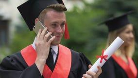 Diploma sorridente dell'università della tenuta dello studente di laurea del maschio, parlante sul telefono archivi video