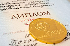 The diploma of university and gold medal. The diploma in the termination of university with is distinguished also a gold medal for successful study Royalty Free Stock Photography