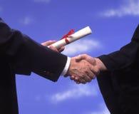 Diploma y apretón de manos de la graduación fotos de archivo libres de regalías