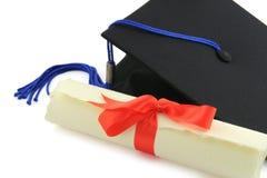 Diploma y casquillo de la graduación Foto de archivo libre de regalías