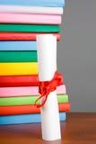 Diploma y pila de libros Fotografía de archivo libre de regalías