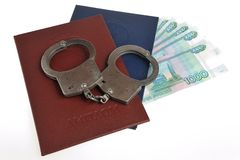 Diplomas of higher education and money with handcuffs isolated Stock Photo