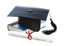 Avläggande av examenhatten, diplom och bokar isolerat på vit Arkivfoto