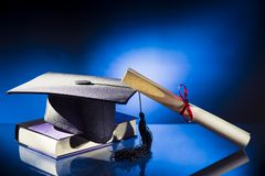 Avläggande av examenhatten, diplom och bokar Arkivfoto