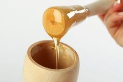 Dipper van de honing op de achtergrond van de bijenhoningraat Honingslekkernij in glaskruik en honingratenwas Stock Afbeeldingen