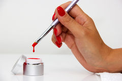 Dipping the brush in nail polishes Stock Photo