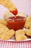 Dipping chicken finger in BBQ sauce. Closeup of dipping chicken finger in BBQ sauce with red and white tablecloth royalty free stock images