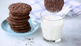 Dipping chocolate cookie in milk. Woman hand dipping chocolate cookie in glass of milk, slow motion stock video footage