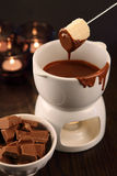 Dipping into chocolate fondue Stock Images