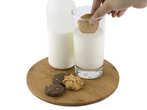 Dipping cookie in glass of milk Stock Image