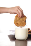 Dipping cookie in milk vertical. Shot of a hand dipping cookie in milk vertical Stock Photography