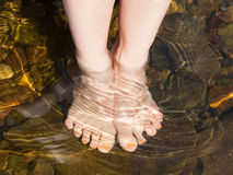 Dipping feet in water off a stone beach Royalty Free Stock Photography