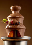 Dipping fresh fruit into a chocolate fountain. Dipping fresh fruit into a chocolate fondue fountain with a skewer of summer fruits dripping sauce in the royalty free stock photos