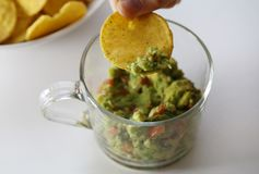 Dipping a Nacho to Homemade Guacamole. Dipping a golden brown corn nacho to fresh homemade guacamole. In this photo the guacamole is served from a glass cup and royalty free stock image