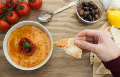 Dipping pita bread in hummus Stock Images