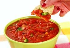 Dipping into salsa with a tortilla chip Stock Photos