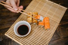 Sushi rolls into soy sauce stock image