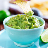 Dipping a tortilla chip in a bowl of guacamole Stock Image