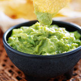 Dipping tortilla chip in guacamole. Inside molcajete bowl stock photography