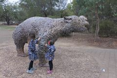 Diprotodon sculpture in Naracoorte Caves National Park South Australia. Two girls Talya and Naomi Ben Ari age 4-8 touching a Diprotodon sculpture,one of the royalty free stock photo