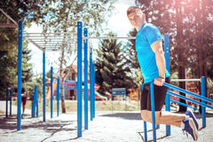 Dips exercise outdoor. Young fit man doing dips exercise outdoor in open air gym. Toned image stock photos