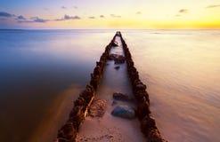 Dique de madera largo en Mar del Norte en la puesta del sol Imágenes de archivo libres de regalías
