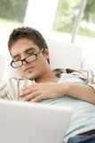 Diríjase al hombre de la tecnología que duerme en el frontal del sofá Imagen de archivo