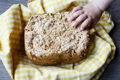 Diríjase el pan hecho del cereal en paño amarillo en la tabla de madera con la mano del niño Fotografía de archivo libre de regalías