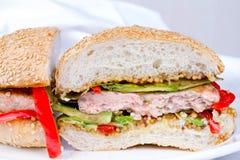 Diríjase la hamburguesa cocinada con el pavo, aguacate, lechuga, cebollas, pimienta roja de la paprika en un bollo de la semilla  Fotos de archivo libres de regalías