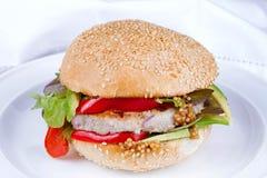 Diríjase la hamburguesa cocinada con el pavo, aguacate, lechuga, cebollas, pimienta roja de la paprika en un bollo de la semilla  Imágenes de archivo libres de regalías