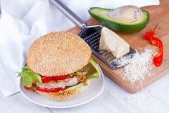 Diríjase la hamburguesa cocinada con el pavo, aguacate, lechuga, cebollas, pimienta roja de la paprika en un bollo de la semilla  Fotografía de archivo