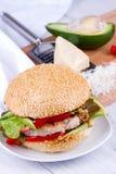 Diríjase la hamburguesa cocinada con el pavo, aguacate, lechuga, cebollas, pimienta roja de la paprika en un bollo de la semilla  Foto de archivo