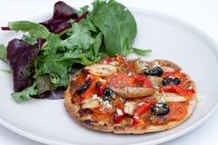Diríjase la mini pizza cocida del vegano con la ensalada del ruccola imagen de archivo libre de regalías