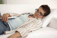 Diríjase la tecnología dormida en el sofá con la computadora portátil Imagenes de archivo